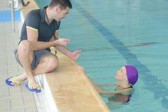 拿着秒表游泳池边有空的中心的游泳教练 免版税库存图片