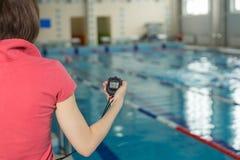 拿着秒表游泳池边的游泳教练在休闲中心 免版税库存图片