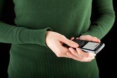 拿着移动电话sms的现有量键入妇女 免版税库存图片
