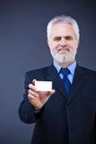 拿着空插件的英俊的商人 免版税库存照片
