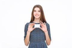 拿着空插件的年轻微笑的女商人画象  免版税库存图片