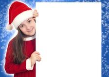 拿着空白横幅的愉快的圣诞节女孩 免版税库存图片