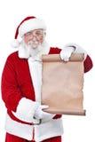 拿着空白滚动列表的圣诞老人 库存照片