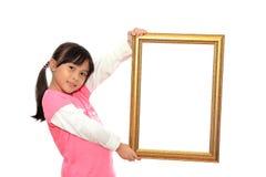 拿着空白画框的女孩 库存图片