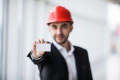 拿着空白的名片的建筑工人在楼房建筑 图库摄影