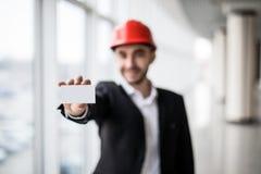 拿着空白的名片的建筑工人在楼房建筑 免版税库存图片