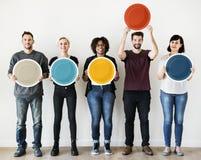 拿着空白的圆的委员会的不同的人民 库存照片