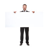 拿着空白的广告牌的商人 免版税库存照片