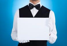 拿着空白的广告牌的男管家 免版税库存照片