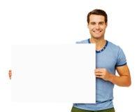 拿着空白的广告牌的英俊的人 免版税库存照片