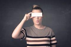 拿着空白的拷贝空间纸的俏丽的女孩在她的眼睛 库存图片