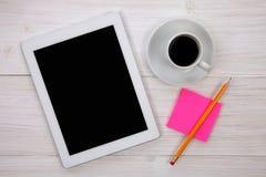 拿着空白的数字式片剂、笔记薄和咖啡的手  库存照片