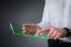 拿着空白的未来派透明片剂个人计算机的手 免版税库存图片