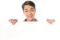 拿着空白的横幅的十几岁的男孩被隔绝在白色 库存照片
