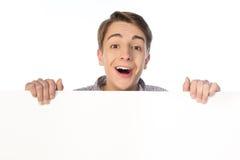 拿着空白的横幅的十几岁的男孩被隔绝在白色 库存图片