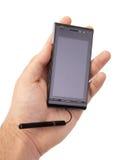 拿着空白的流动智能手机的手 免版税图库摄影