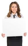 拿着空白的海报的年轻女商人 免版税库存图片