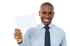 拿着空白的白色卡片的微笑的非洲人 免版税库存图片