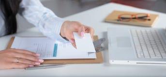 拿着空白的白色名片的年轻女商人画象  免版税库存图片