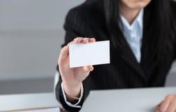 拿着空白的白色名片的年轻女商人画象  免版税图库摄影