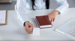 拿着空白的白色名片的年轻女商人画象  免版税库存照片