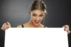 拿着白色广告牌的激动的妇女 免版税库存图片