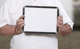 拿着空白的白色板岩的人 免版税库存照片
