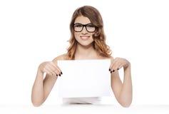 拿着空白的白色标志的微笑的少妇 免版税库存图片