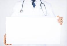 拿着空白的白色横幅的医生 免版税库存图片