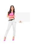 拿着空白的白色纸板的少妇 免版税库存图片