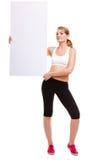 拿着空白的空的广告横幅的健身运动的妇女 库存图片