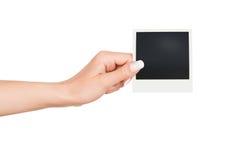 拿着空白的立即照片的手 免版税库存照片