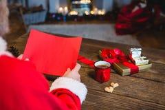 拿着空白的红色纸的圣诞老人 库存照片