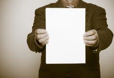 拿着空白的纸片的商人。企业概念。 图库摄影