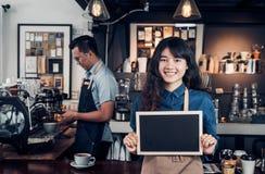 拿着空白的黑板咖啡菜单的亚洲女性barista穿戴斜纹布围裙在与同事的逆酒吧有微笑面孔的,咖啡馆 库存照片