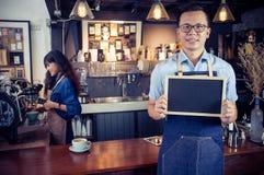 拿着空白的黑板菜单的微笑的亚洲barista画象  免版税图库摄影