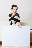 拿着空白的介绍委员会的沙发的妇女 免版税库存照片