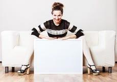 拿着空白的介绍委员会的沙发的妇女 免版税库存图片