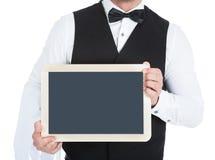拿着空白石板的男管家 免版税库存照片
