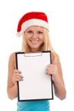 拿着空白董事会的圣诞老人帽子的少妇 免版税图库摄影