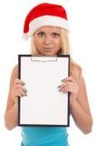拿着空白董事会的圣诞老人帽子的少妇 免版税库存图片
