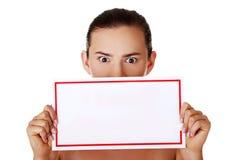 拿着空白董事会的震惊妇女 免版税库存照片