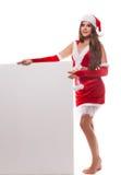 拿着空的公猪的圣诞老人帽子的美丽的年轻圣诞节妇女 免版税库存照片