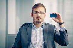 拿着空的名片的商人在办公室 免版税库存图片