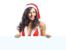 拿着空的委员会的圣诞老人帽子的圣诞节妇女 免版税图库摄影