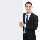 拿着空的委员会的微笑的亚裔商人 免版税库存照片