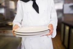 拿着空的板材的一位女性厨师的中间部分在厨房里 免版税库存照片