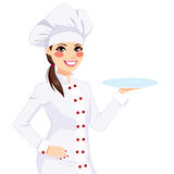拿着空的板材的女性厨师 免版税库存照片