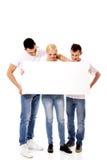 拿着空的横幅的小组愉快的朋友 免版税库存图片
