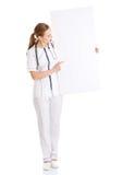 拿着空的白板的美丽的白种人护士或医生。 免版税库存照片